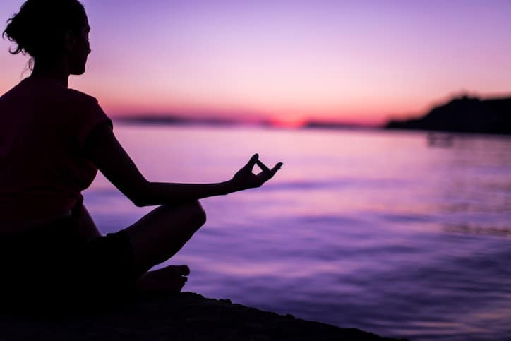 Young Woman Meditating By Peaceful Sea