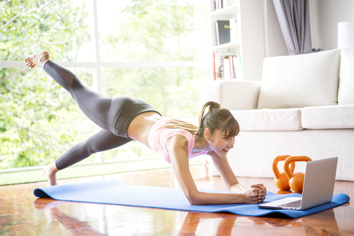 Woman exercising at home with computer